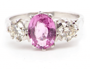 A three stone pink sapphire and diamond ring